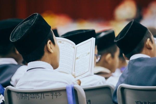 Anak laki-laki baju putih membaca Al-Quran wakaf - Zakat.or.id