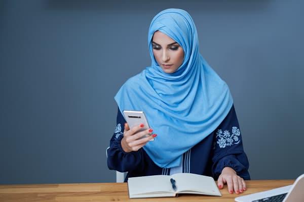 Perempuan muslim melakukan Wakaf digital di Dompet Dhuafa melalui smartphone